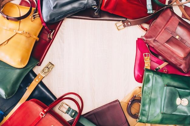Kolorowe skórzane torby ułożone na stole. widok z góry stołu z torbami. sklep z wyrobami skórzanymi. skórzana walizka niebieska, czerwona, żółta, zielona.