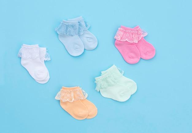 Kolorowe słodkie skarpetki niemowlęce na niebieskim tle. akcesoria dla niemowląt. leżał płasko.