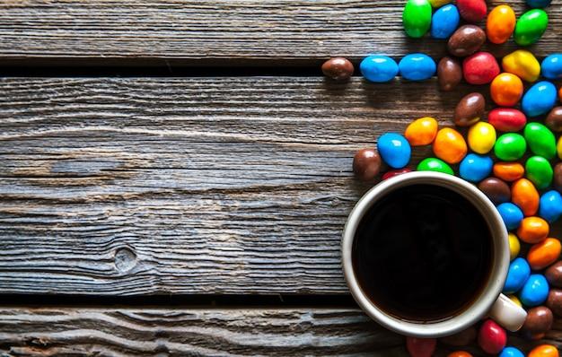 Kolorowe słodycze z kawą na tle drewnianych i