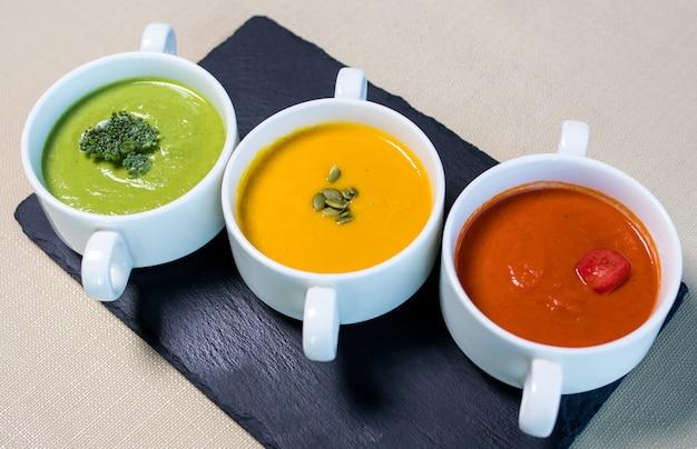 Kolorowe smaczne zupy na czarnym talerzu