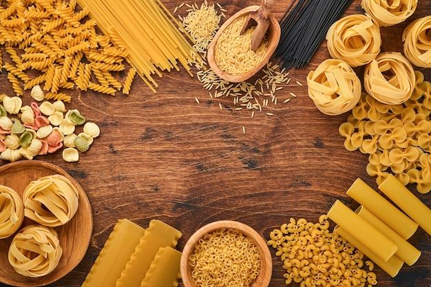 Kolorowe spaghetti, tagliatelle, farfalle, penne, ptititm, noodle, fusilli, cannelloni na starym drewnianym tle