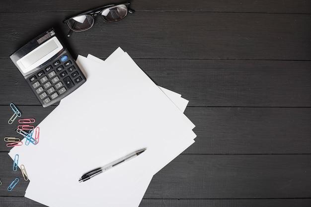 Kolorowe spinacze do papieru; biały papier; długopis; kalkulator i okulary przeciwsłoneczne na czarnym drewnianym tle