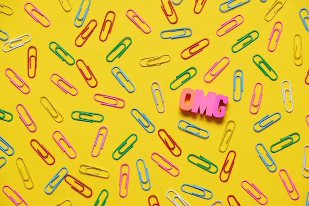 Kolorowe spinacze na żółtym tle i litery omg
