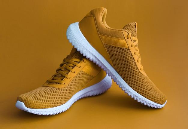 Kolorowe sportowe buty na musztardowym kolorze