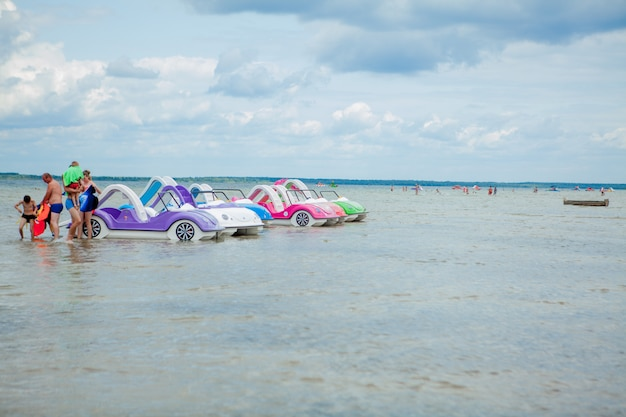 Kolorowe stare zabytkowe katamarany z tworzyw sztucznych i łodzie w pobliżu drewnianego molo na brzegu dużego jeziora