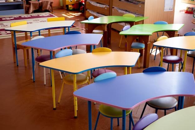 Kolorowe stoły dla dzieci w zbliżeniu przedszkola.