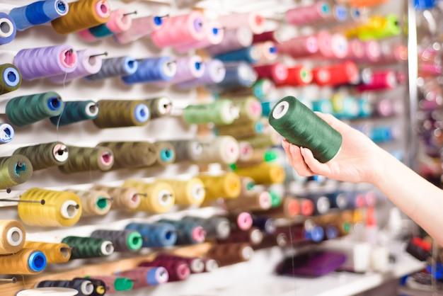 Kolorowe stożki i szpule nici w atelier. krawiectwo, przemysł odzieżowy, koncepcja warsztatu projektanta.