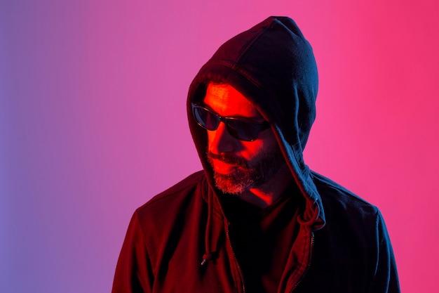 Kolorowe studio portret brodatego mężczyzny z okularami przeciwsłonecznymi na tle czerwonym i niebieskim.