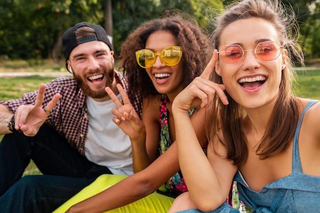 Kolorowe stylowe szczęśliwe młode towarzystwo przyjaciół siedzących w parku, mężczyzny i kobiet, którzy razem bawią się