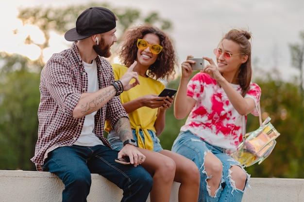 Kolorowe stylowe szczęśliwe młode towarzystwo przyjaciół siedzi w parku