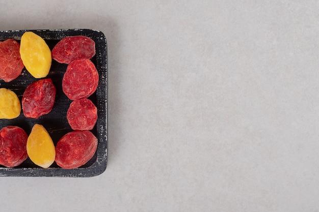 Kolorowe suszone jagody na drewnianym talerzu.