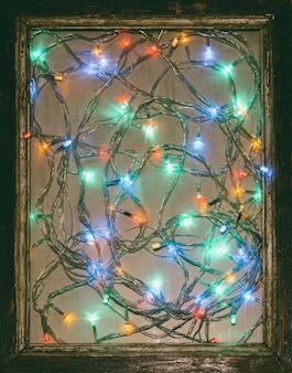 Kolorowe światła świąteczna girlanda świąteczna w starej drewnianej ramie.
