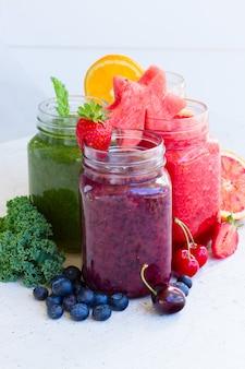 Kolorowe świeże jagody i owoce smoothy napoje w szklanych słoikach ze składnikami na białym stole