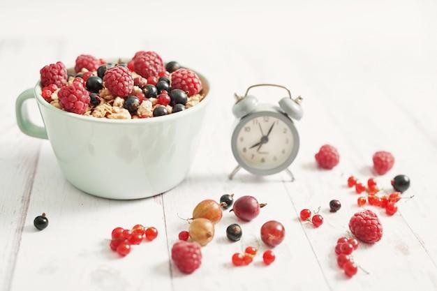 Kolorowe świeże jagody z płatkami w białej filiżance i budziku