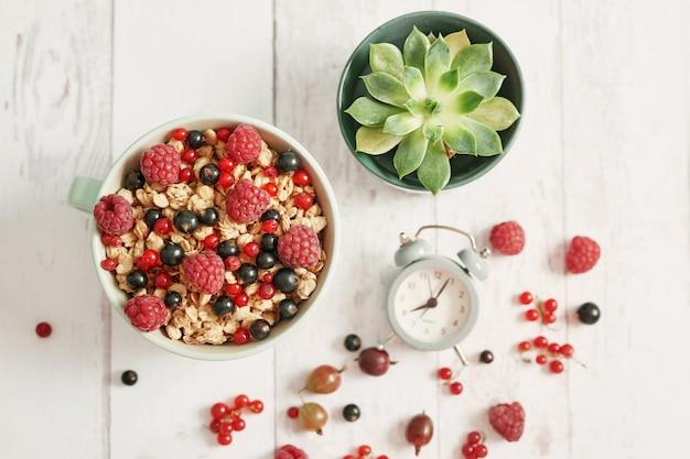 Kolorowe świeże jagody z płatkami w białej filiżance, kaktusie i budziku