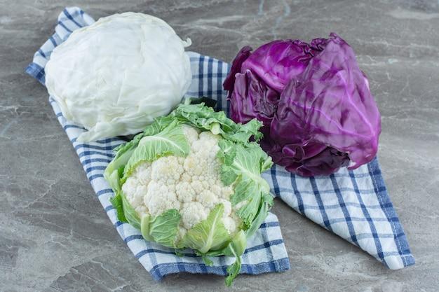 Kolorowe świeże organiczne kapusty na szarym stole.