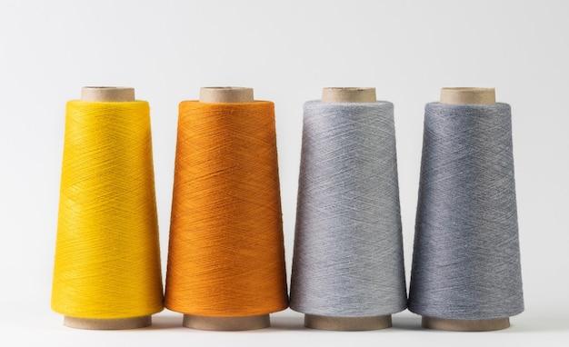 Kolorowe szpulki nici z rzędu na białym tle