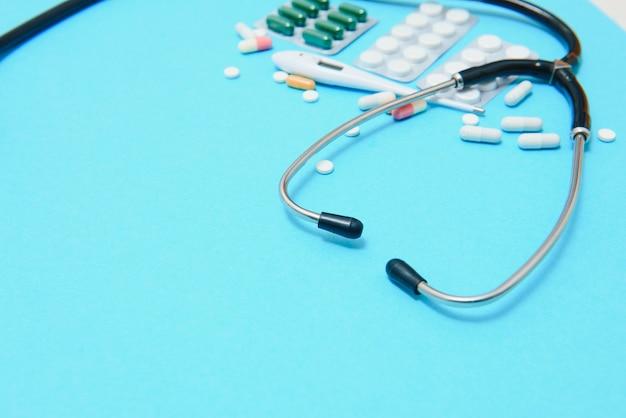 Kolorowe tabletki i kapsułki w pudełku, termometr, statoskop, butelka antyseptyczna, pojemnik, tabletki w opakowaniu, znajdują się po obwodzie obrazu na niebieskim tle