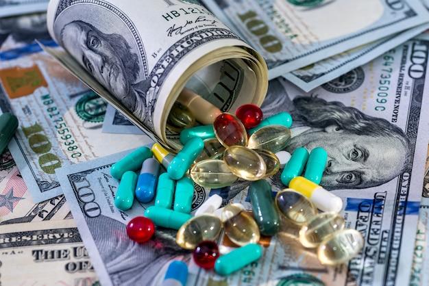 Kolorowe tabletki na zbliżenie banknotów dolarowych
