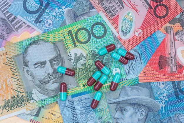 Kolorowe tabletki w kapsułkach na banknotach dolara australijskiego