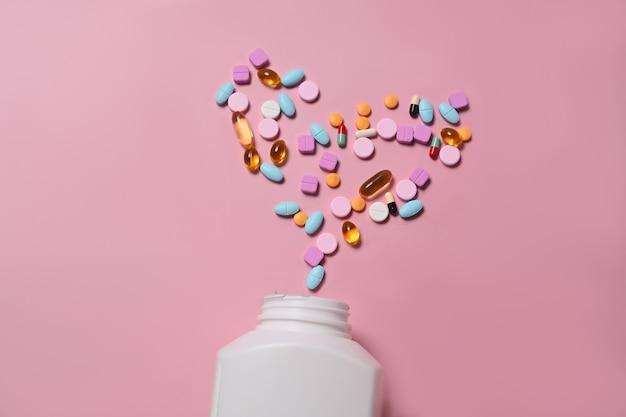 Kolorowe tabletki wysypujące się z butelki pigułki na różowym tle.