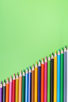 Kolorowe tęczowe ołówki na limonkowym zielonym tle