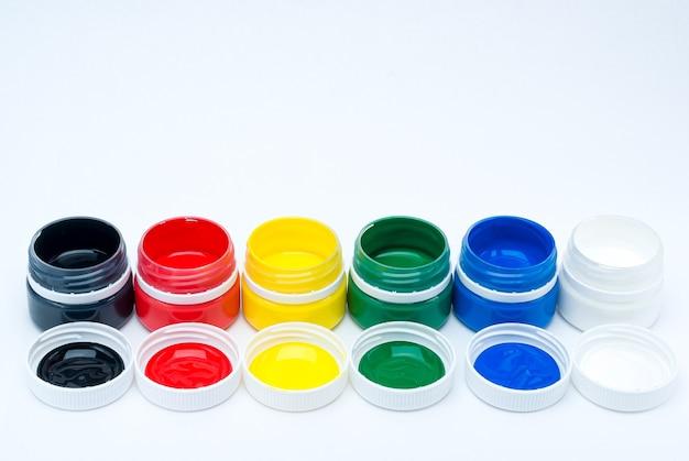 Kolorowe tętniące życiem puszki farby gwasz na białym tle