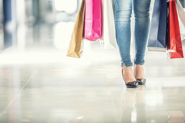 Kolorowe torby na zakupy w rękach kobiety kupujących i jej nogi dżinsy i buty.