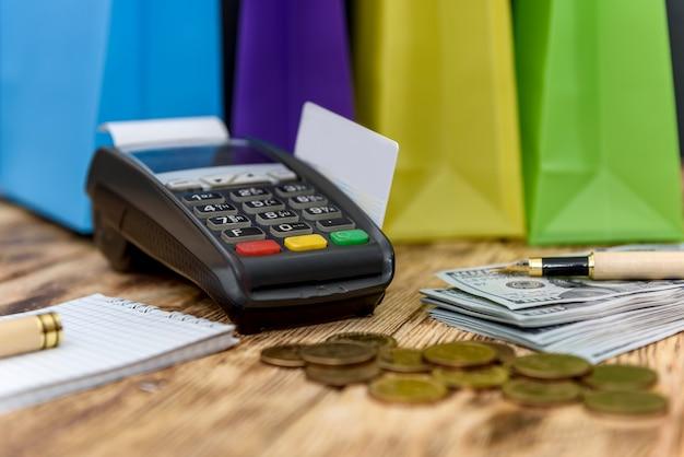 Kolorowe torby na zakupy z terminalem i banknotami dolarowymi