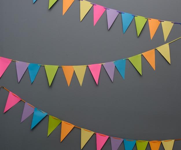 Kolorowe trójkątne flagi firmowe na linie na ciemnoszarej ścianie