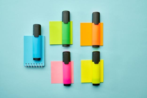 Kolorowe trwałe markery i notesy na niebieskim tle. artykuły biurowe, akcesoria szkolne lub edukacyjne, narzędzia do pisania i rysowania