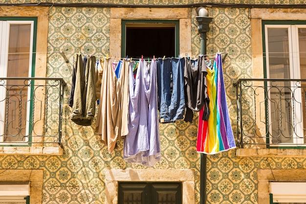 Kolorowe ubrania schną w oknie