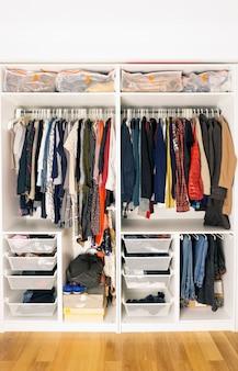 Kolorowe ubrania w szafie. przechowywanie odzieży i rzeczy w szafie