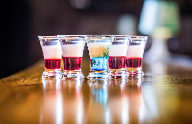 Kolorowe ujęcia w klubie. napój alkoholowy w różnych kolorach. strzały przy stole barowym. napoje alkoholowe w kieliszkach. shoty tequili, wódka, whisky. zestaw koktajli alkoholowych w kieliszkach.