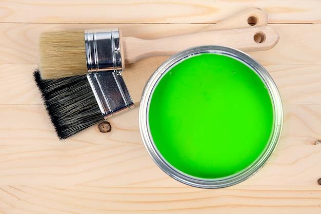 Kolorowe wiadro zielonej farby z dwoma pędzlami na drewnianym stole