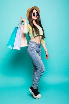 Kolorowe wibracje zakupowe. pełne portrety uśmiechniętej brunetki kobiety w kapeluszu i jasnych ubraniach z uruchomionymi torbami na zakupy