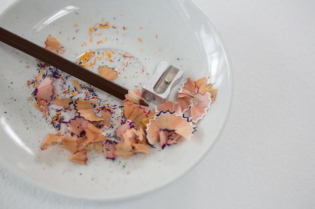 Kolorowe wióry z brązowym ołówkiem i temperówką w spodeczku