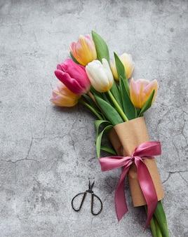 Kolorowe wiosenne tulipany na betonowym biurku