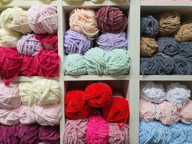 Kolorowe włóczki lub kłębki z różnych rodzajów wełny do dziania na półkach w sklepie pasmanteryjnym...