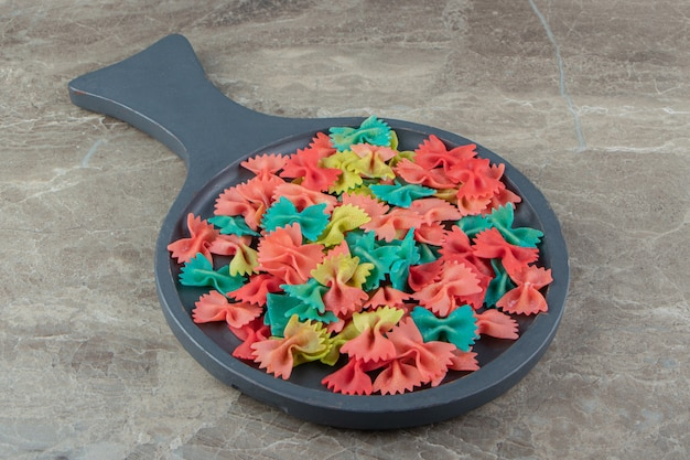 Kolorowe wstążki makaron na desce.