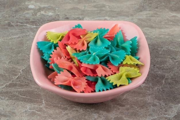 Kolorowe wstążki makaronowe w różowej misce