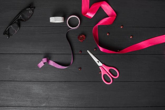 Kolorowe wstążki; nożycowy; perła i czarne okulary na drewnianym stole czarny