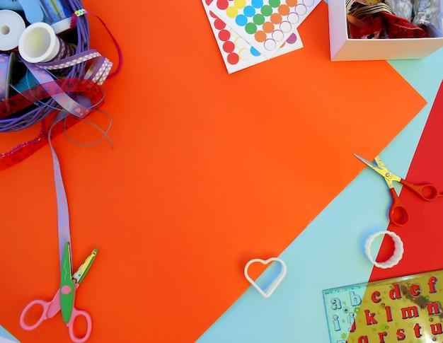 Kolorowe wstążki, pudełko z wątkami, foremki, nożyczki i linijki z literami na kolorowe bac