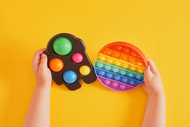 Kolorowe zabawki proste wgłębienie i pop go w dłoniach dziecka na żółtym tle, zmysłowa zabawka do rozwijania umiejętności motorycznych rąk