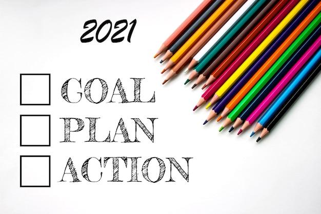 Kolorowe zaostrzone ołówki z bliska na białym tle na białym tle z napisem 2021, cel, plan, działanie. zestaw rysunków szkolnych. kolekcja wielokolorowych ołówków. selektywne skupienie.