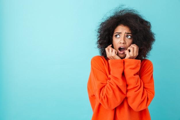 Kolorowe zbliżenie obrazu emocjonalnej kobiety z kręconymi włosami, patrząc w górę na copyspace z szokiem i otwartymi ustami, odizolowane na niebieskiej ścianie