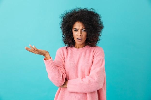 Kolorowe zbliżenie obrazu oburzonej kobiety z fryzurą afro, rzucającej dłoń i wyrażającej nieporozumienie, odizolowane na niebieskiej ścianie