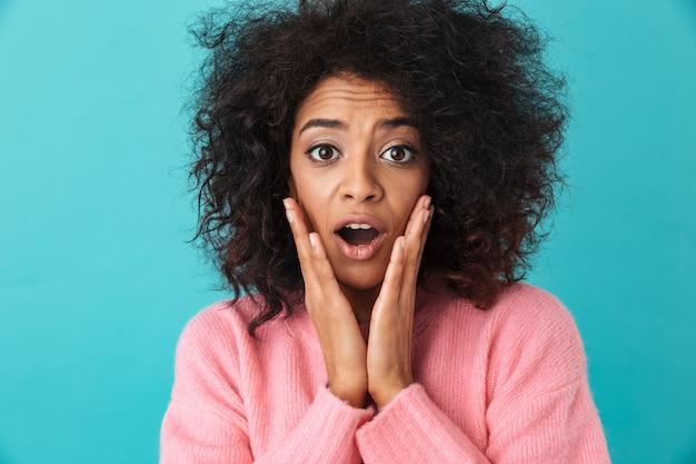 Kolorowe zbliżenie obrazu zaskoczonej kobiety chwytając twarz z podekscytowanym wyglądem i otwartymi ustami, odizolowane na niebieskiej ścianie