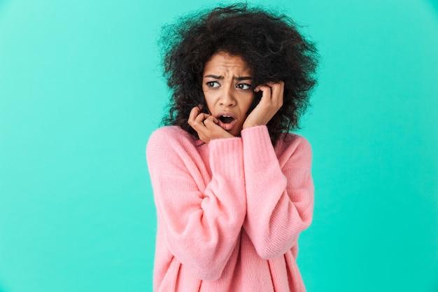 Kolorowe zbliżenie obrazu zdezorientowanej kobiety w różowej koszuli, patrząc na bok i wyrażające strach lub frustrację, odizolowane na niebieskiej ścianie