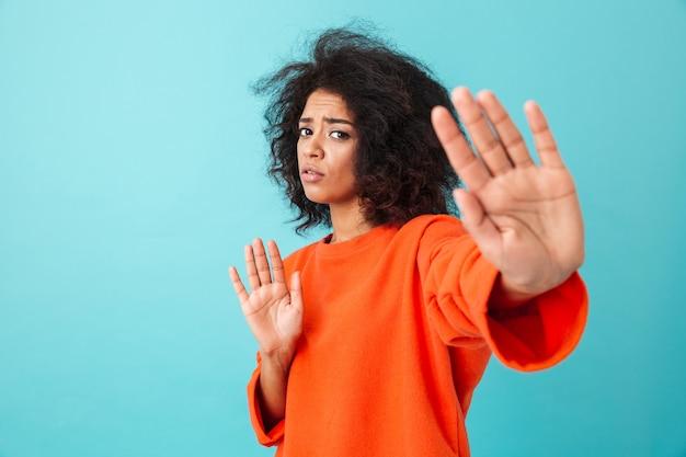 """Kolorowe zbliżenie wizerunku zdeterminowanej kobiety wyrażającej zakłopotanie i zmieszanie, pokazując gesty stopu i mówiąc """"nie"""", odizolowane na niebieskiej ścianie"""